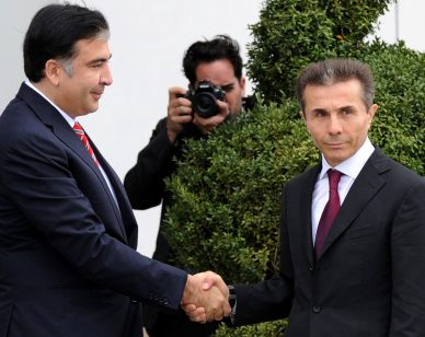 Georgia's President Mikheil Saakashvili (L) shakes hands with the leader of Georgian Dream opposition coalition Bidzina Ivanishvili (R) as they meet in Tbilisi, on October 9, 2012. Ivanishvili?s coalition defeated Saakashvili's ruling party at parliamentary polls last week. AFP PHOTO / VANO SHLAMOV